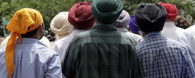 Members of the Sikh community, many wearing turbans, listen to New York City Mayor Mike Bloomberg speak to the media at the Sikh Cultural Society in the Queens borough of New York, Monday, Aug. 6, 2012. New York City's mayor and police commissioner have expressed their condolences at the Sikh Cultural Society in Queens following Sunday's mass shooting in Wisconsin. (AP Photo/Seth Wenig)